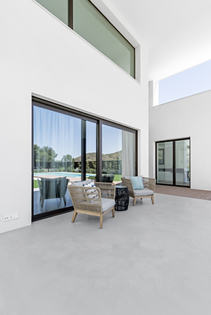 Exterior area with light grey microcement floor and two armchairs with a central table in front of a window.